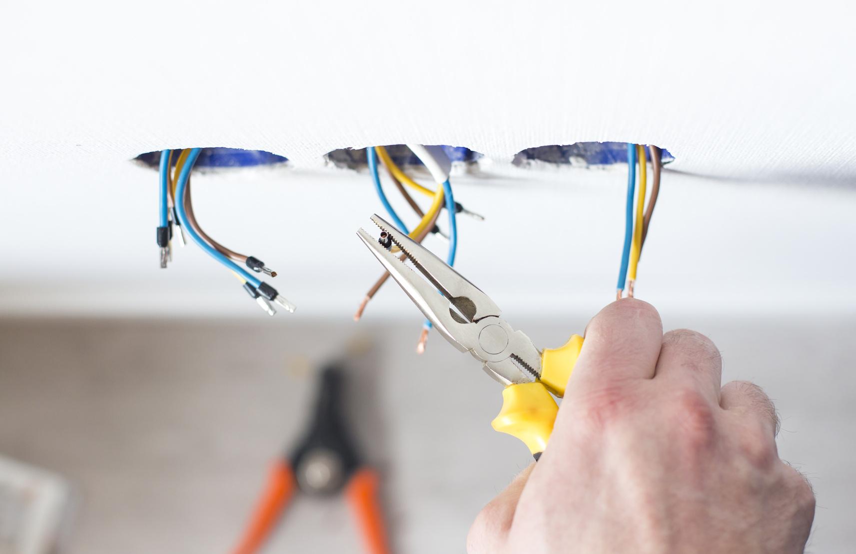 Male hands repair the socket